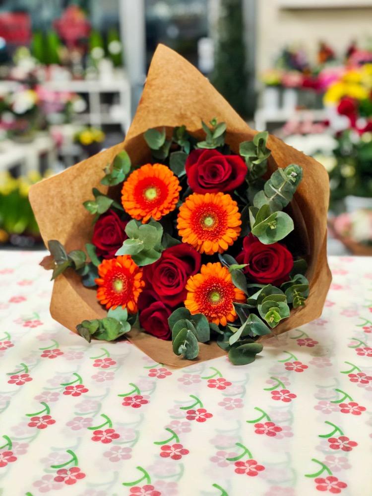 Červené růže, gerbery a eukalyptus